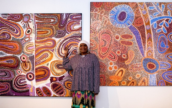 female artist stands in front of two purple, red and orange coloured painting