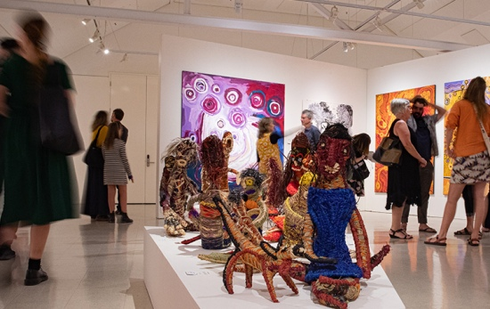 crowds walk through busy gallery, foreground shows woven sculptures of goannas and women sitting
