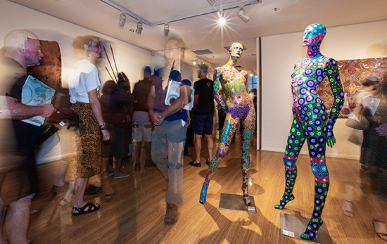crowds walk through busy gallery, foreground shows two mannequins painted in an aboriginal dot painting style