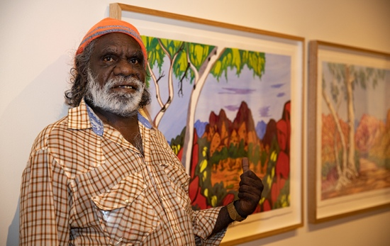 male artist stands in front of watercolour painting of central australia