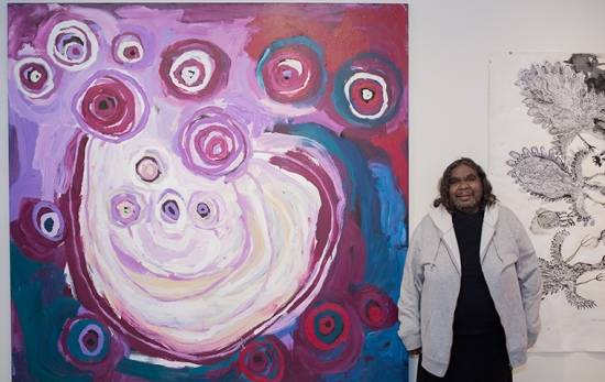 female artist stands in front of purple painting