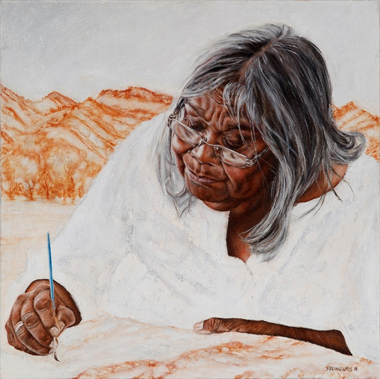 aboriginal women painting with orange hills behind her