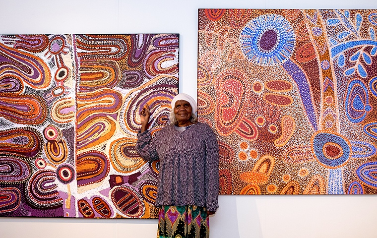 aboriginal artist standing in front of two red coloured artworks pointing to the painting she created