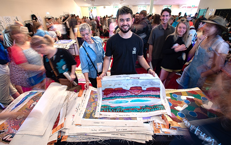 man holding up aboriginal artwork canvas in the midst of a busy marketplace