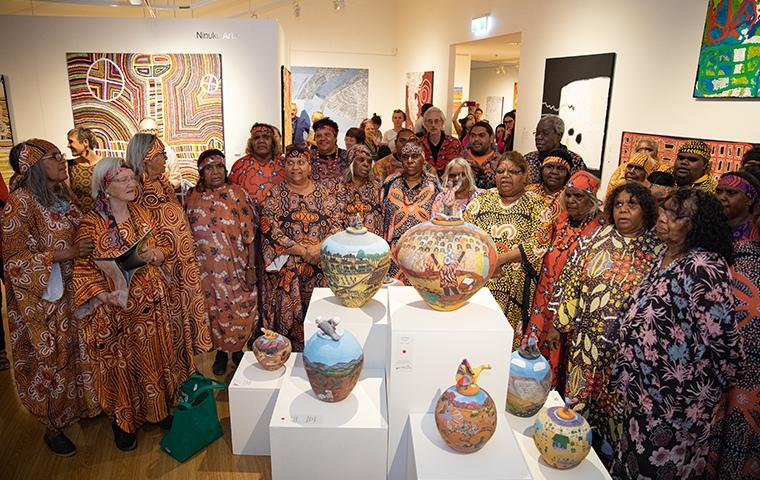 aboriginal women's choir stand around pots singing