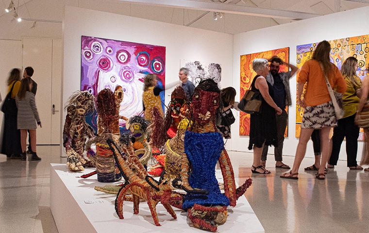 soft sculptures in foreground, in background crowds look at pink and orange aboriginal artworks