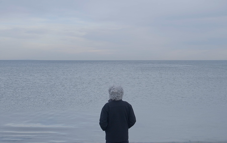 man has his back to camera stares at ocean