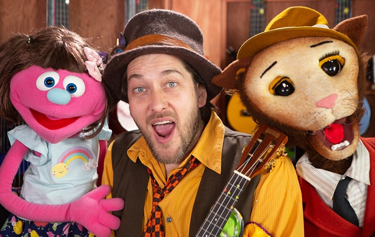 man posing with pink female-identifying puppet and and cat like puppet wearing a hat