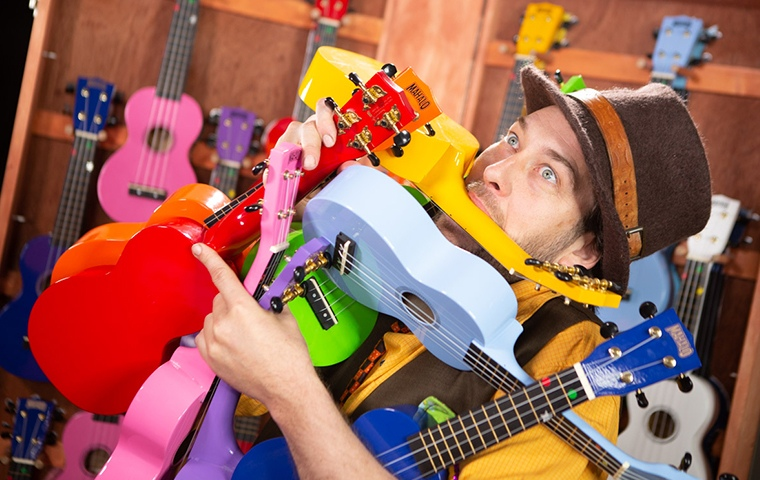 man struggling to hold an armful of colourful ukuleles