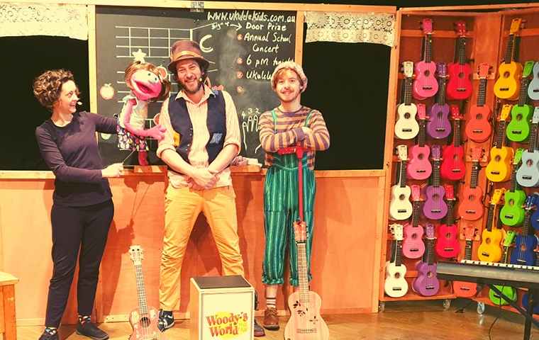 woman operating pink female-identifying puppet stand with 2 men in front of chalkboard and wall of colourful ukuleles