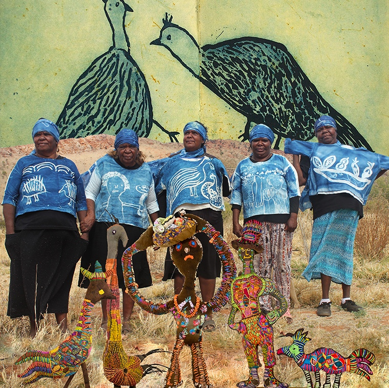 Aboriginal women standing in their blue tie-dyed shirts, foreground is soft colourful sculptures