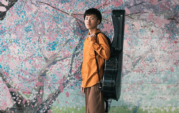japanese man standing in front of painted cherry blossom tree with guitar case on back